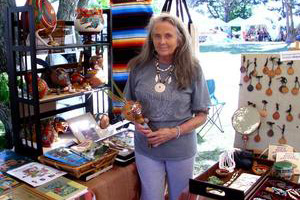 a woman standing with assorted native american merchandise