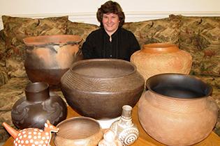a woman with several pieces of pottery